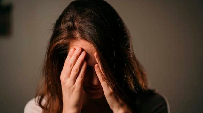 Imagem de mulher cabisbaixa, com as mãos na testa encobrindo os olhos, em postura de preocupação.